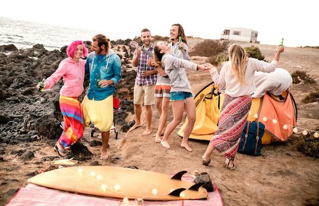 Друзья-хипстеры веселятся вместе на пляжной вечеринке во время кемпинга