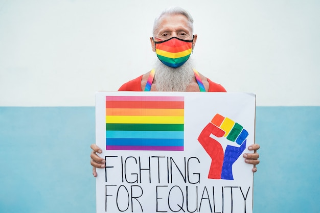 Hipster gay senior man with rainbow mask holding banner at lgbt pride
