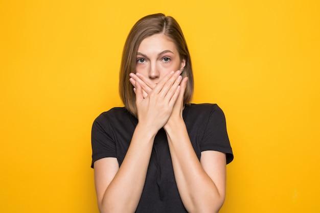 流行に敏感な女の子は彼女の手で口を覆います。若い驚きの女性