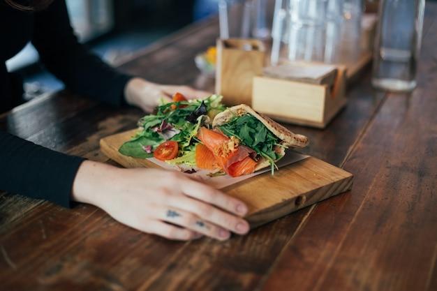 Ragazza hipster mangia panino al salmone in pita greca