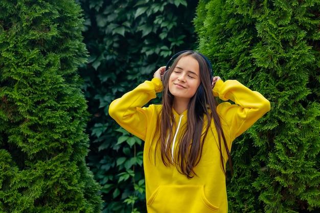 화창한 날 무선 헤드폰으로 좋아하는 음악을 즐기는 힙스터 소녀
