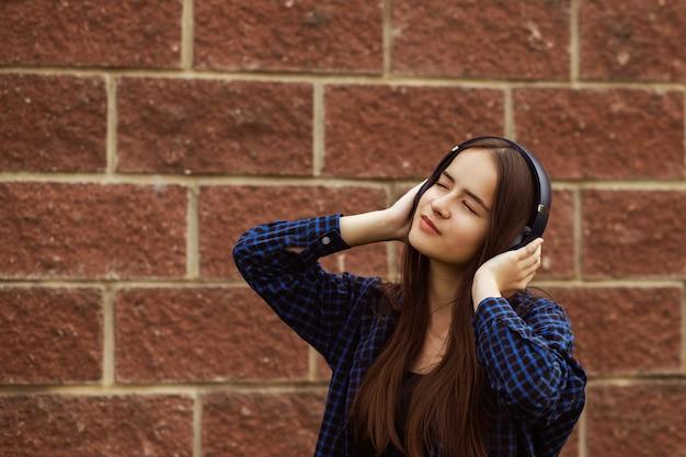 Hipster girl enjoys favorite music song in wireless headphones