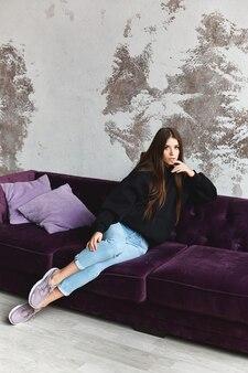 黒のスウェットシャツとブルージーンズのソファに座って、屋内でカメラを見て内気な少女。インテリアにカジュアルな服装の若い女性