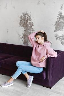 ピンクの空のパーカーと屋内でポーズをしながらソファに座っているブルージーンズの内気な少女。カジュアルな服装の若い女性