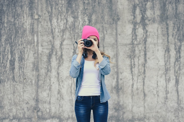 Hipster girl in jeans clothing and pink hat taking photo against grey concrete wall. focus on camera