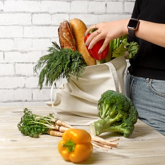 Hipster girl putting greens and fresh leek on the kitchen table out of the cotton reusable tote bag, using eco shopper instead of a plastic bag, concept of healthy lifestyle