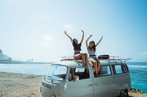 Hipster girl relaxing on the retro van roof in her summer road t