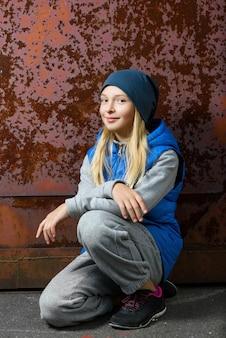 さびた壁に床に座っている内気な少女