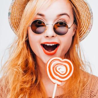롤리팝으로 웃는 힙스터 소녀. 청소년 여가 재미