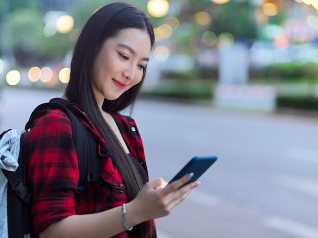 流行に敏感な女の子の観光客が交通機関を待っている電話で通りの向こう側にオンラインタクシーを予約する