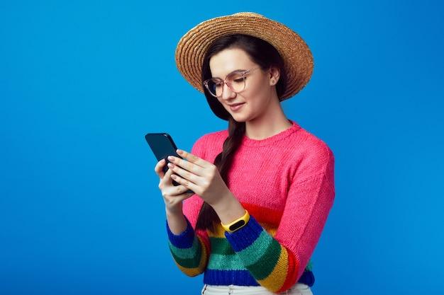 Хипстерская девушка набирает текстовое сообщение на сотовом телефоне и наслаждается онлайн-общением