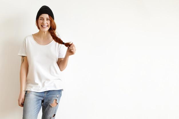 Ragazza hipster che indossa un cappello nero elegante, t-shirt bianca e jeans stracciati sorridendo allegramente