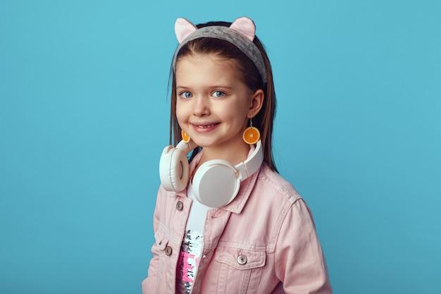 Хипстерская девушка в розовых наушниках и оранжевых серьгах улыбается