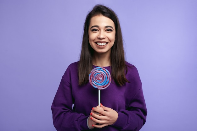 Hipster girl with big candy smiling over bright violet