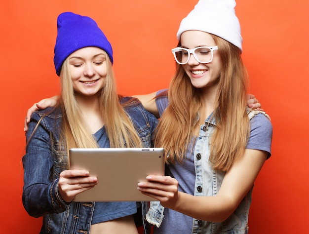 Hipster girls friends taking selfie with digital tablet, studio