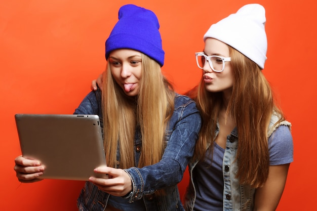 Hipster girls friends taking selfie with digital tablet