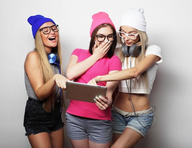 白い壁の上のデジタル タブレットで流行に敏感な女の子の友達