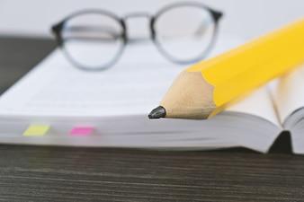 大きな黄色の鉛筆で開いた本を読むための流行に敏感なメガネ