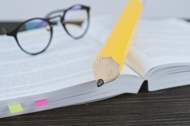 Hipster glasses for reading on an open book with big yellow pencil