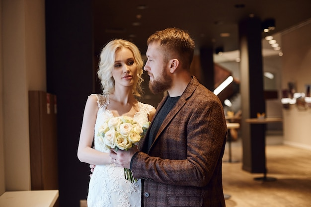 流行に敏感な新郎と新婦、愛と忠誠。恋愛中のカップルは、結婚式の日に抱擁とキスをします。理想的なカップルは夫婦になる準備をしています。お互いを見つめている男女がクローズアップ