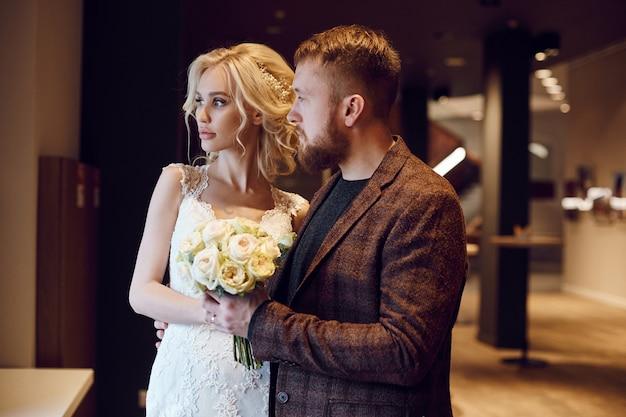 Хипстерский жених и невеста, любовь и верность. влюбленная пара объятия и поцелуи в день свадьбы. идеальная пара готовится стать мужем и женой
