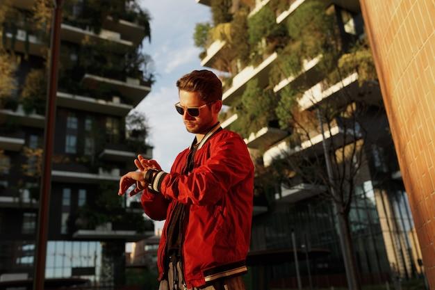 Хипстерский парень одет в классную одежду, гуляя по улице, глядя на часы, днем, в зданиях.