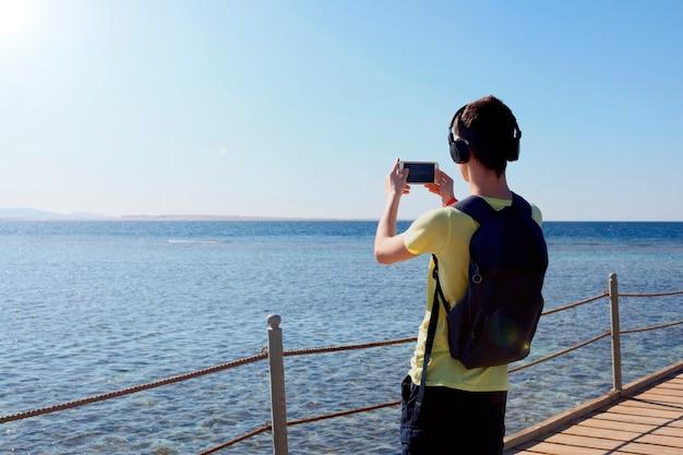 헤드폰을 끼고 바다 근처 바위의 모바일 스마트 폰 디지털 카메라로 놀라운 풍경 사진을 찍는 힙스터 남자, 아름다운 태양 빛은 문자 메시지를 위한 복사 공간이 있는 배경을 만듭니다.