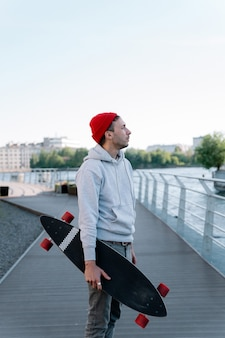 Hipster guy with longboard on city bridge trendy man hipster skateboarder hold skateboard in hand