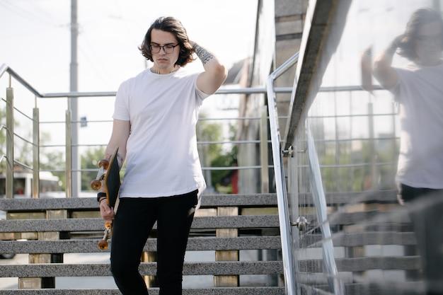 あなたのロゴやカジュアルな都会的なスタイルのデザインのためのスペースと白い空白のtシャツを着ている流行に敏感なハンサムな男性モデル