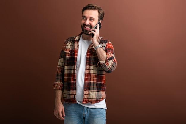 Uomo barbuto alla moda bello hipster su colore marrone