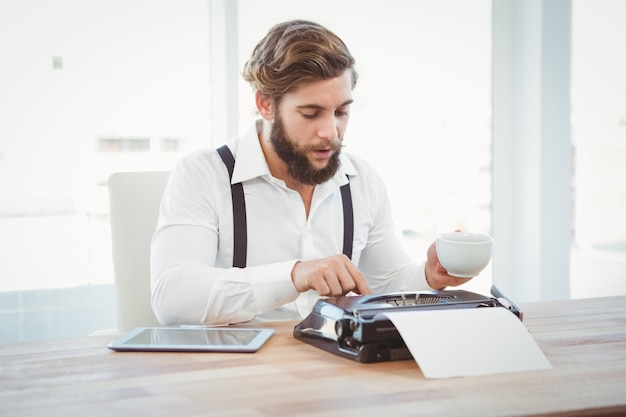 Hipster holding coffee working on typewriter