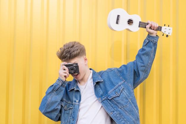 デニムジャケットのヒップスターがウクレレを手に持ち、古いフィルムカメラで写真を撮ります。