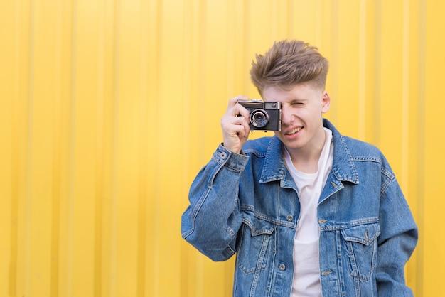 ジーンズのジャケットのヒップスターは黄色の壁にあり、レトロなフィルムカメラで写真を撮っています。