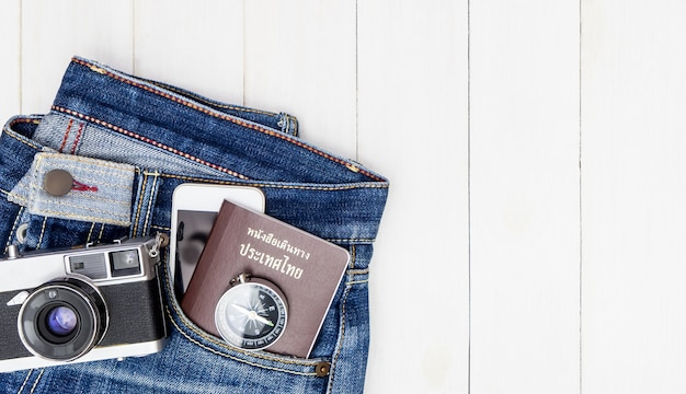 Hipster jean with travel objects and equipment on wooden copy space
