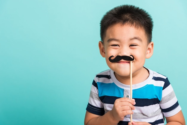 Hipster kid holding black mustache close face