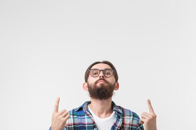 Хипстерский образ жизни и люди концепции, молодой хипстерский человек указывает вверх на белом фоне с копией пространства