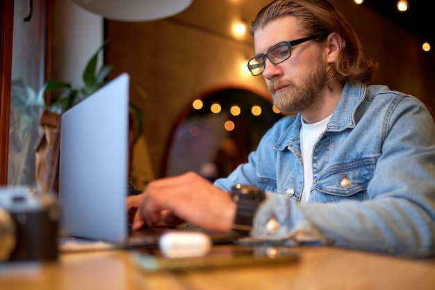 Hipster lifestyle and creative workspace,confident guy working on laptop in coffee shop