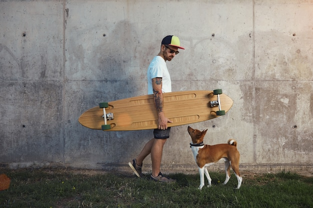 Hipster longboarder and a young brown and white basenji dog looking at one another next to a gray concrete wall