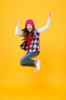 Хипстерский вид. веселый ребенок в вязаной шапке. джинсовый модный стиль. школьница на желтом фоне. полный энергии. детская мода и красота. подросток прыгает в одежде повседневного стиля. счастливое детство.