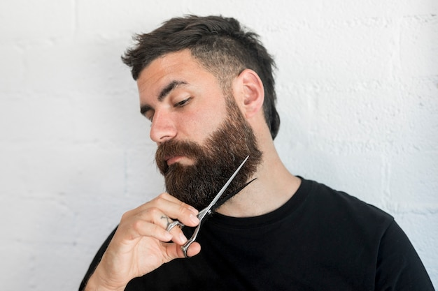 Hipster male cutting beard with scissors