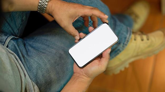 Хипстерский мужчина-фрилансер сидит в кафе и использует макет экрана мобильного телефона смартфона