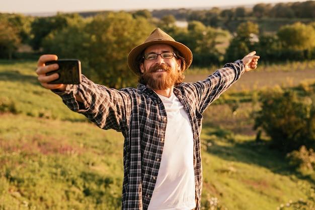 Hipster male trekker taking selfie with smartphone for travel blog