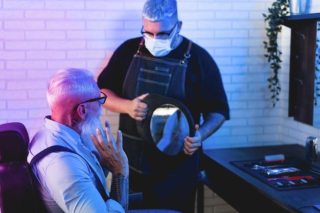 Hipster man checking hair and beardcut inside barber shop during coronavirus outbreak
