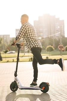 Битник человек добирается до работы через город на электрическом скутере. экологичный транспорт. скоростной электротранспорт. человек, едущий на эскутере. экология и городской образ жизни