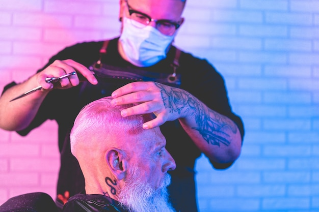 Hipster man getting hair cut at vintage barber shop while wearing face protective masks