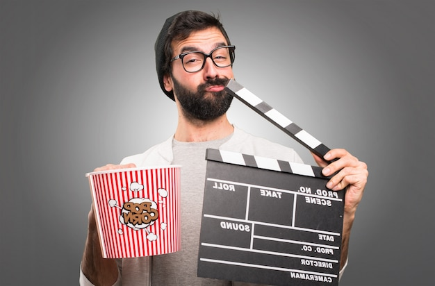 Hipster человек держит clapperboard на сером фоне