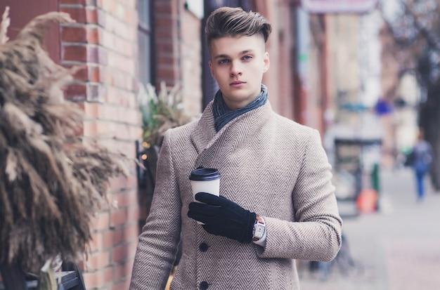 Хипстерский мужчина в осеннем пальто, пьющий кофе на городской улице