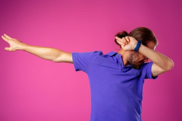ピンクの背景に軽くたたくダンスポーズの流行に敏感な男クローズアップ