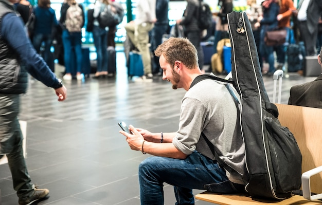 Hipster man at international airport using mobile smart phone