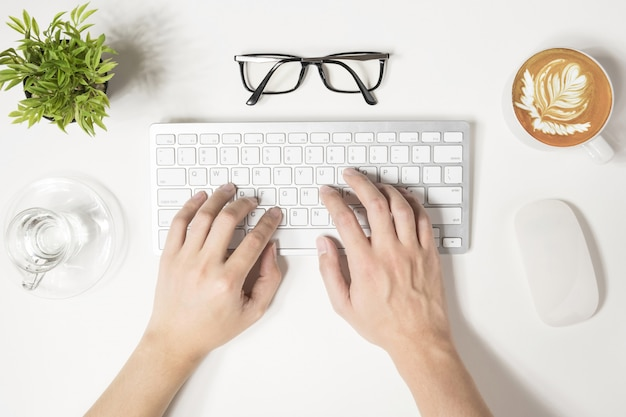 Hipster man is typing on computer keyboard, top view.